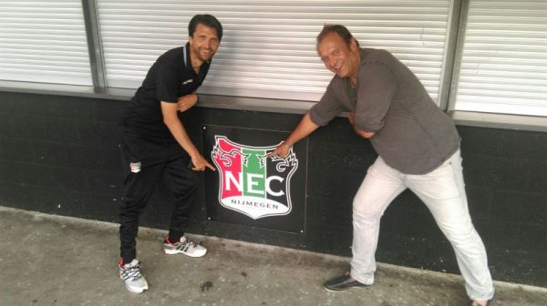 Peter Hyballa und Klaus Veltmann zeigen auf das Wappen von NEC Nijmegen