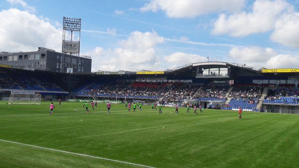 Fußballplatz mit Spielern drauf. Grüner Rasenplatz und dahinter eine Zuschauertribüne.