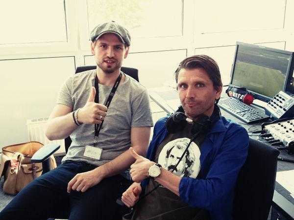 """Uli Hebel und Peter Hyballa sitzen nebeneinander in einem Raum mit Tontechnik und zeigen die """"Daumen hoch"""" Geste."""