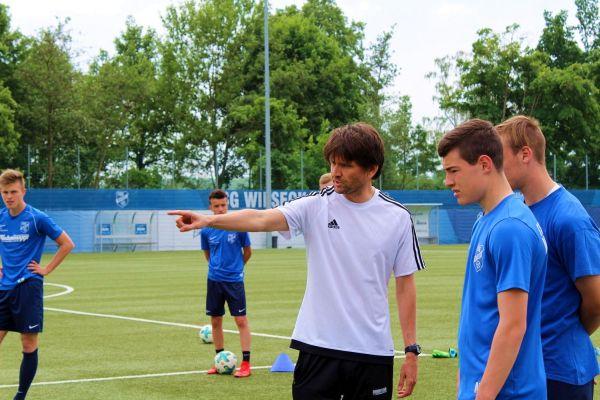 Peter Hyablla im Training auf dem Fußballplatz. Er zeigt mit dem Finger nach links und erklärt einem Spieler was.