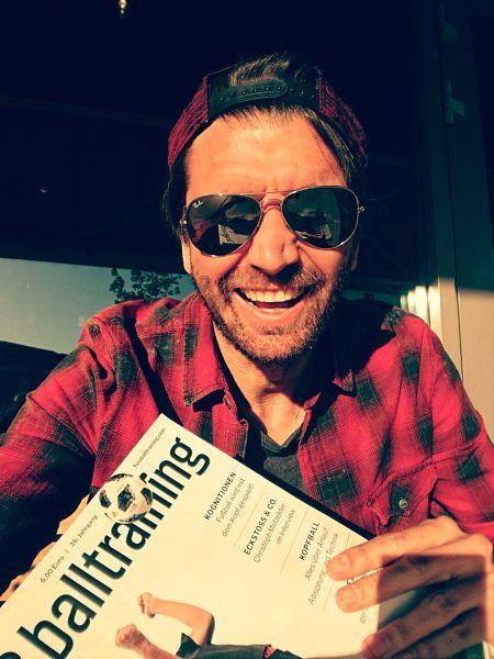 Peter Hyballa hat eine Fußballzeitschrift in der Hand und lacht in die Kamera. Er trägt eine Baseballkappe und eine verspiegelte Sonnenbrille.