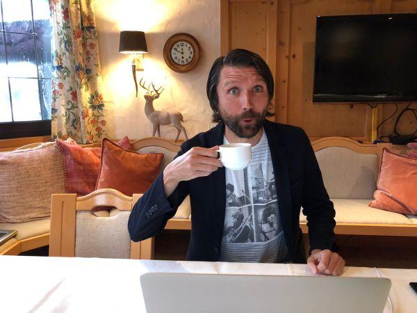 Peter sitzt in einem Cafe und trinkt Kaffee