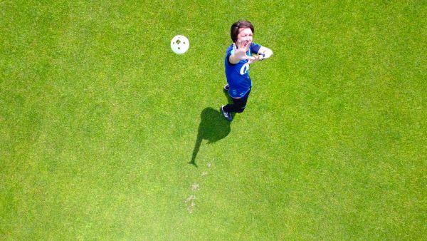 Ein Bild aus der Vogelperspektive. Peter Hyballa steht auf grünem Rasen und schaut erschrocken nach oben zum Betrachter.